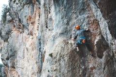 Mężczyzna w hełmie wspina się skałę Zdjęcia Stock