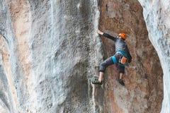 Mężczyzna w hełmie wspina się skałę Obrazy Royalty Free