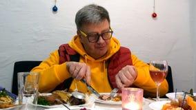 Mężczyzna w jaskrawych oczu szkłach i ubraniach je mięso z pomocą noża i rozwidlenia zdjęcie wideo