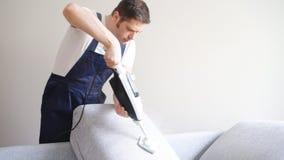 Mężczyzna w jednolitej cleaning tkaninie kanapa zbiory wideo