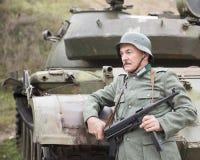 Mężczyzna w jednolitym Niemieckim żołnierzu WW II z armatnim Schmeisser Zdjęcie Stock