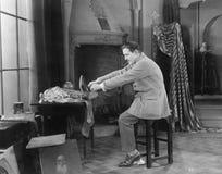 Mężczyzna w jego pracownianym kładzeniu na butach (Wszystkie persons przedstawiający no są długiego utrzymania i żadny nieruchomo Zdjęcie Royalty Free