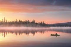 Mężczyzna w kajaku na rzece na scenicznym zmierzchu obraz royalty free