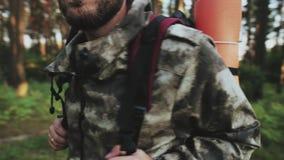 Mężczyzna w kamuflaż pozyci w lesie z plecakiem i patrzeć wokoło Turystyczna samiec wybiera ścieżkę iść zdjęcie wideo