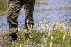 Mężczyzna w kamuflażu munduru pozyci na kwiatu polu Fotografia Royalty Free