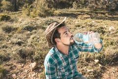 Mężczyzna w kapeluszowej wodzie pitnej w polu fotografia royalty free