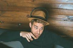 Mężczyzna w kapeluszu i hełmofonach robi śmiesznym twarzom obraz royalty free