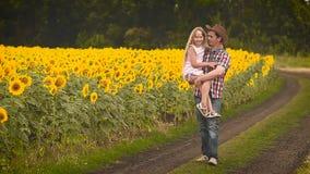 Mężczyzna w kapeluszu znosi córki w ręce wzdłuż pola z słonecznikami zbiory wideo