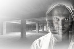 Mężczyzna w kapiszonie łączył z pustym przemysłowym wnętrzem obraz stock