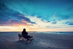 Mężczyzna w kapiszonu obsiadaniu na osamotnionej ławce na plaży zdjęcia royalty free