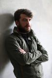 Mężczyzna w khakiej kurtce opiera na ścianie z krzyżować rękami zakończenie W górę czerń Zdjęcia Royalty Free
