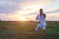 Mężczyzna w kimonie trenuje karate przy zmierzchem, kopia przestrzeń kawaler obrazy stock