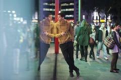 Mężczyzna w koloru żółtego puloweru pozyci, opiera na ścianie szklany M&M sklep na Piccadilly cyrku Słucha muzyka na hełmofonach Zdjęcie Royalty Free