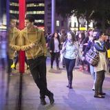 Mężczyzna w koloru żółtego puloweru pozyci, opiera na ścianie szklany M&M sklep na Piccadilly cyrku Słucha muzyka na hełmofonach Zdjęcia Stock
