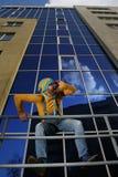 Mężczyzna w kombinezonach na tło glassed budynku Obrazy Royalty Free
