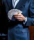 Mężczyzna w kostium pozach z kartami na drewnianym tle obrazy stock