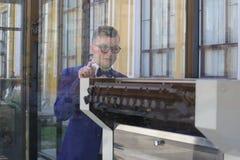 Mężczyzna w kostiumu błękitnych spojrzeniach przy drukową prasą za szkłem obrazy royalty free