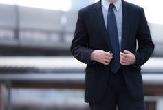 Mężczyzna w kostiumu g mężczyzna w kostiumu przygotowywa dla spotkania Jest stojący jego kurtkę i dotykający Odosobniona i odbitk Obrazy Royalty Free