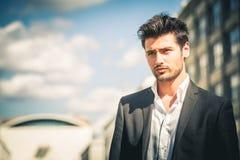 Mężczyzna w kostiumu i białym koszulowym patrzeć Outdoors na ulicie w mieście zdjęcia stock