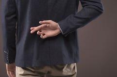 Mężczyzna w kostiumu krzyżował jego palce za jego z powrotem fotografia royalty free