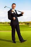 Mężczyzna w kostiumu mienia piłce i golfa drewnie Fotografia Stock