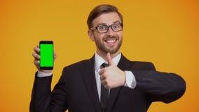 Mężczyzna w kostiumu mienia smartphone z zieleń ekranem, seans aprobat biznesu app zbiory wideo