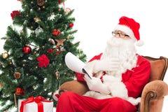 Mężczyzna w kostiumu Santa Claus z notepad Zdjęcia Stock