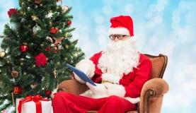 Mężczyzna w kostiumu Santa Claus z pastylka komputerem osobistym Obrazy Royalty Free