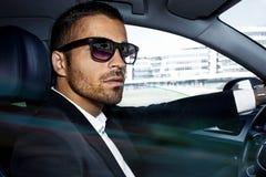 Mężczyzna w kostiumu siedzi przy kołem samochód fotografia royalty free