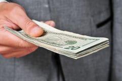 Mężczyzna w kostiumu z zwitkiem dolary Obrazy Royalty Free