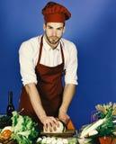 Mężczyzna w kucbarskim kapeluszu i fartuchu ciie kapusty Cook pracuje w kuchennym pobliskim stole z warzywami i narzędziami fotografia royalty free