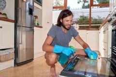 Mężczyzna w kuchennym cleaning piekarniku fotografia royalty free