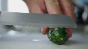 Mężczyzna w Kuchennym rozcięciu Z nożem ogórek w plasterkach dla Świeżej sałatki zdjęcie stock