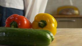 Mężczyzna w kuchni robi zakupy dla pakunków warzyw pomidory, ogórki i papryka, w górę, zwolnione tempo zbiory