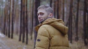 Mężczyzna w kurtce chodzi przez jesieni lasowego zwolnionego tempa, filmowy strzał zdjęcie wideo