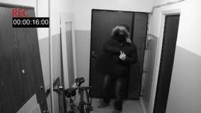 Mężczyzna w masce łama drzwi wewnątrz i strzela chowaną kamery krócicę zdjęcia royalty free