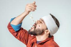 Mężczyzna w medycznych bandaża mienia pigułkach w ręce Obraz Royalty Free