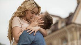 Mężczyzna w miłości trzyma dziewczyny i całuje ona tenderly, romantyczny związek, data zdjęcia stock