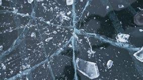 Mężczyzna w mitynkach roztrzaskuje lód na lodzie swobodny ruch Kamera rusza się za lodem Kawałek lód jest bardzo zbiory