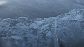 Mężczyzna w mitynkach roztrzaskuje lód na lodzie swobodny ruch Kamera rusza się za lodem Kawałek lód jest bardzo zbiory wideo