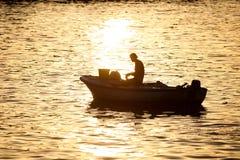 Mężczyzna w motorowej łodzi przy zmierzchem Obraz Royalty Free