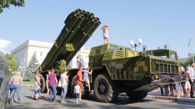 Mężczyzna w mundurach chodzą w mieście wśród ludzi blisko wielkiej militarnej maszyny na ulicie zbiory