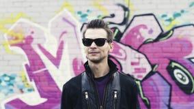 Mężczyzna w okularach przeciwsłonecznych gestykuluje, macha, głowę w kamerze Hip Hop Graffiti izolują na tle subkultura zbiory