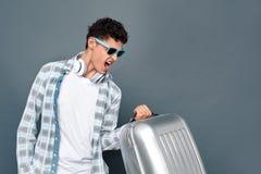 Mężczyzna w okularach przeciwsłonecznych odizolowywających na szarość izoluje turystyki pojęcia trwanie udźwig w górę walizki krz zdjęcie stock