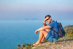 Mężczyzna w okularach przeciwsłonecznych siedzi na krawędzi góry zdjęcie stock