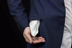Mężczyzna w pingback obraca jego kieszeni inside i trzyma monetę w jego ręce - out, zakończenie obrazy royalty free