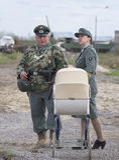 Mężczyzna w postaci śródpolnej żandarmerii i dziewczyny w mundurze niemiec z pram Odbudowa epizod Zdjęcia Stock