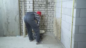 Mężczyzna w pracy odzieży i czerwonym nakrętki gipsowaniu wietrzył betonowy blok ścianę zbiory