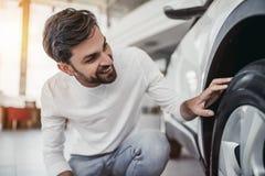 Mężczyzna w przedstawicielstwie firmy samochodowej, Egzamininuje frontowego koło fotografia royalty free