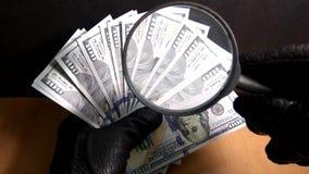 Mężczyzna w rękawiczkach egzamininuje sto dolarowych rachunków przez powiększać - szkło zbiory wideo